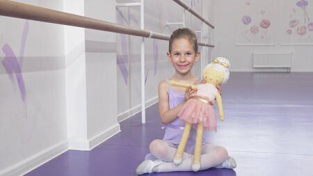 Full length shot of a lovely little ballerina waving to the camera playing with a doll