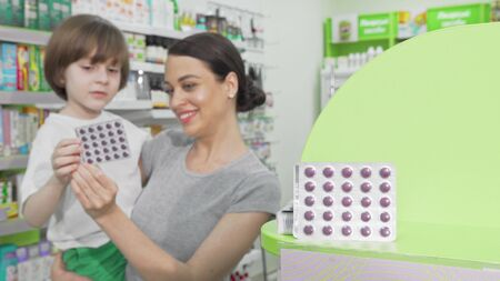 Beautiful woman shopping for medicament pills with her little son