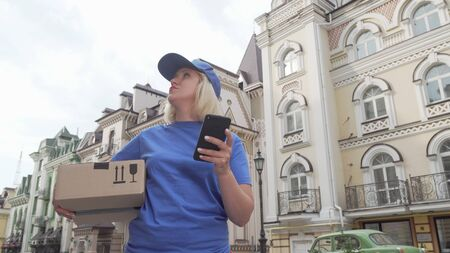 Delivery woman with parcel box using smart phone online map