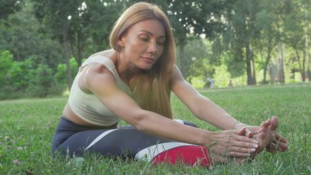 Gorgeous athletic woman stretching outdoors smiling to the camera Imagens - 132061755