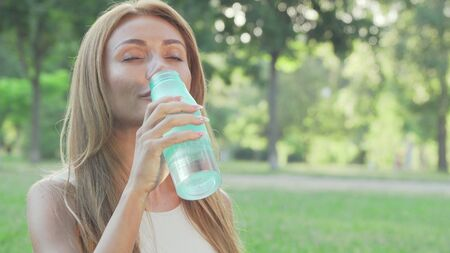 Healthy fit woman drinking water while doing yoga in the park