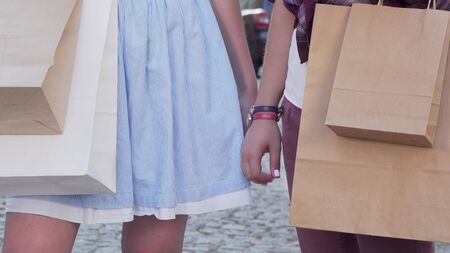 Cropped shot of two female friends holding hands