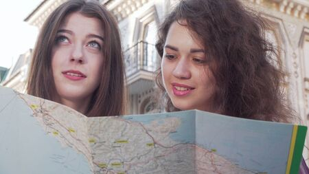 Cropped shot of two young women using a map
