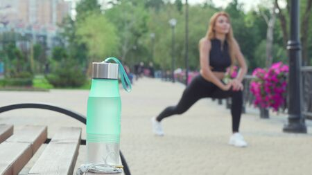 Water bottle on the foreground fit woman stretching outdoors on the back