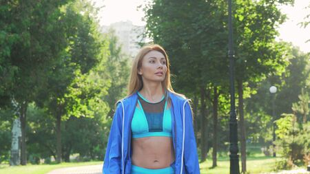 Beautiful sportswoman warming up before jogging in the park
