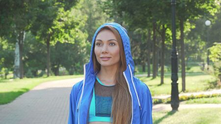 Attractive sportswoman taking off the hood before running in the park Banco de Imagens