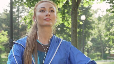 Athletic woman stretching in the park before her morning workout Banco de Imagens