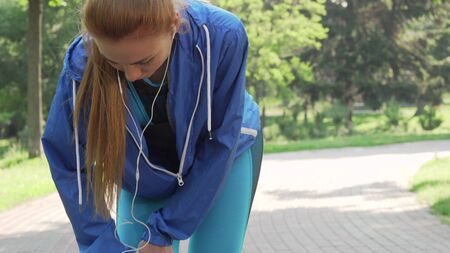 Cropped shot of a female athlete rubbing her injured knee after running Banco de Imagens