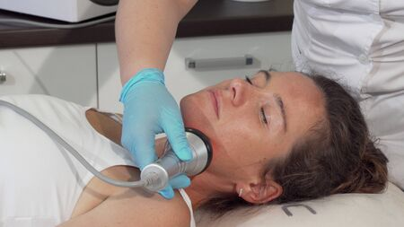 Mature lovely woman getting face rf-lifting treatment Archivio Fotografico - 131967796