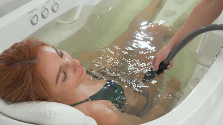 Charming woman relaxing while getting hydromassage at spa Banco de Imagens