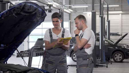 Two car mechanics discussing automobile with open hood