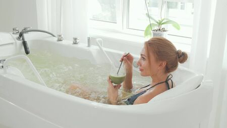 Rear view shot of a woman drinking detox smoothie sitting in hydromassage bath