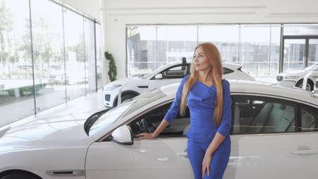 Attractive elegant woman looking away dreamily standing near new car Reklamní fotografie