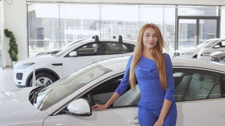 Sexy beautiful woman smiling to the camera standing near new car at dealership
