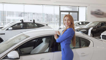 Gorgeous long haired woman stroking new expensive automobile at dealership