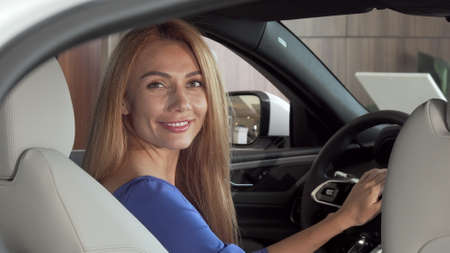 Gorgeous happy woman sitting in expensive new car smiling to the camera