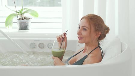 Charming woman drinking detox smoothie sitting in whirl pool bath Banco de Imagens