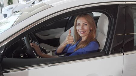 Beautiful female driver smiling to the camera sitting in a new car at the dealership
