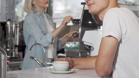 Cropped shot of a man taking cup of coffee from female barista 写真素材