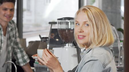Young woman smiling to the camera after getting a cup of coffee at the coffee shop Banco de Imagens