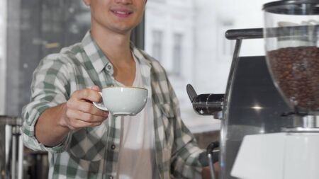 Happy male barista smiling holding out cup of tasty coffee to the camera Banco de Imagens