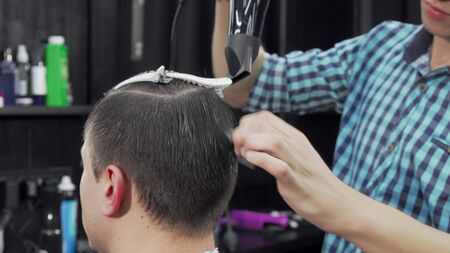 Unrecognizable man getting his hair blow dried by the barber