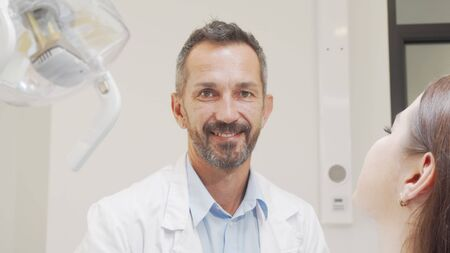 Charming male dentist smiling to the camera while working with patient Banco de Imagens