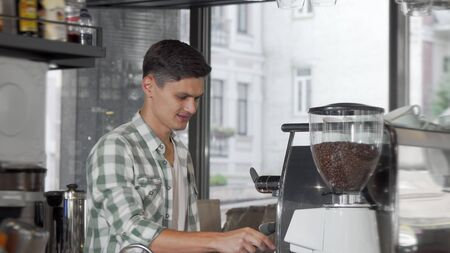Handsome cheerful male barista preparing coffee for clients at his cafe