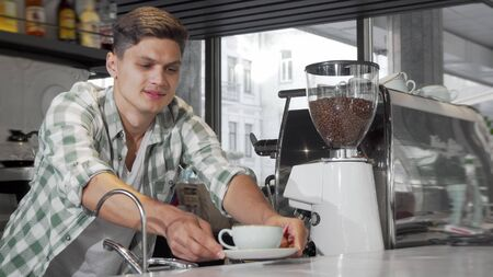 Handsome male barista smiling to the camera after serving delicious coffee