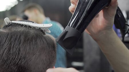 Cropped shot of a barber using blow dryer while styling hair of a client