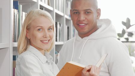 Happy multiethnic couple smiling to the camera while reading a book Banco de Imagens