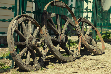Three old wagon wheel standing at the fence.