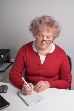 An elderly woman writes a letter to the white table.