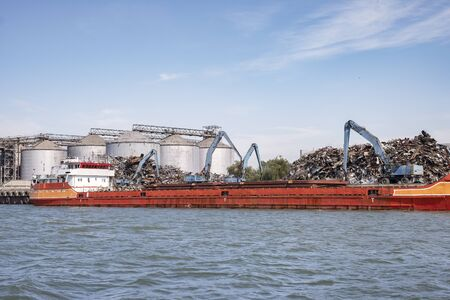 Loading of scrap metal on a ship in the port. The barge is being loaded,