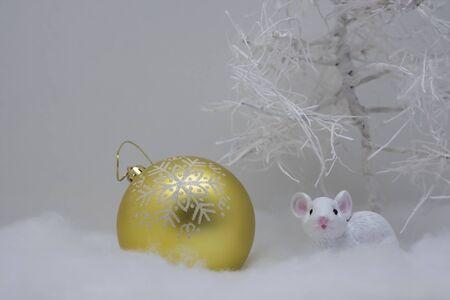Carta bianca fatta a mano con vacanze invernali. Mouse bianco con palla d'oro su sfondo bianco giocattolo. buon anno, buon Natale.