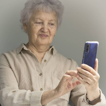 joyful older woman smiles and takes selfie. An old woman with white hair and beige clothes