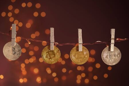 New year financial concept. On a garland on clothespins bitcoins hang. Brown background in the lights from the garlands.