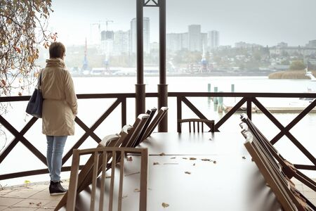lonely woman stands in an abandoned restaurant on the river Bank and looks at the city in the distance.