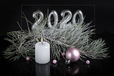 Christmas mysterious composition in dark colors. burning candle, pink ball on the background of fir branch and asilver 2020