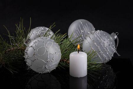 White candle and Christmas balls lie near Christmas tree on dark background Reklamní fotografie - 135492711