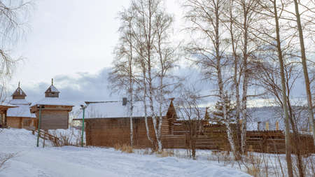 Ancient wooden huts in winter. Snow-covered village, with its white birches Stock Photo