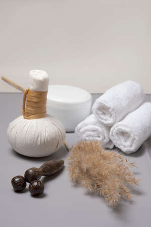 Spa composition of herbal massage bags, a jar of oil and a hand-held wooden massager