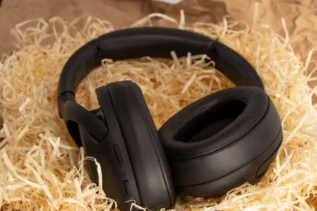 fashionable stereo headphones in black. top view, lie in paper shavings.