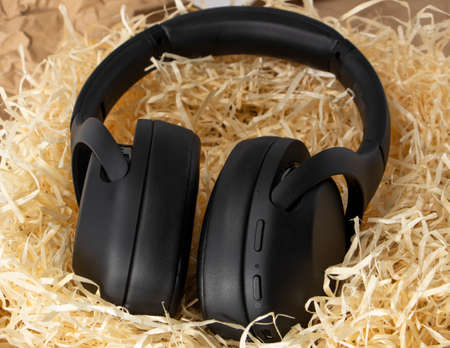 black stereo headphones in gift tinsel, paper shavings