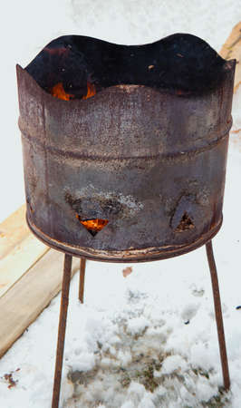a rusty barrel with burning coals stands on the snow. Fire from a barrel.