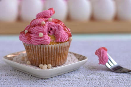 a cupcake beautifully decorated with pink cream and sugar decor