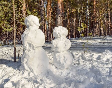 Snowman in the winter landscape in the forest. Undecorated snowman. Two snowmen.