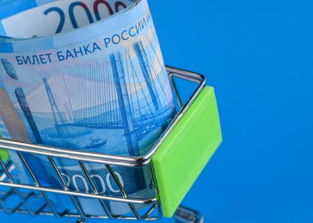 Russian rubles in a trolley on a blue background. Grocery basket and 2000 ruble bills. Russian currency. Side view. Selective focus. Copy space