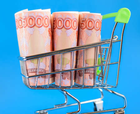 Russian rubles in a trolley on a blue background. Grocery basket and Russian rubles. Russian currency. Selective focus Stock fotó
