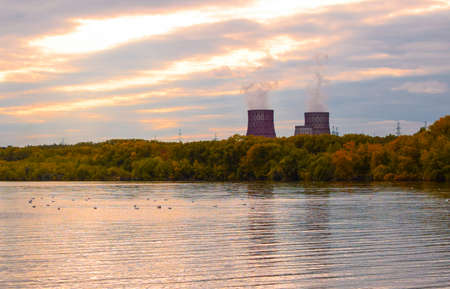 Industry and nature. Colorful sunset over water and forest. Environmental pollution. Thermal power plant with huge chimneys. Selective focus, blur.